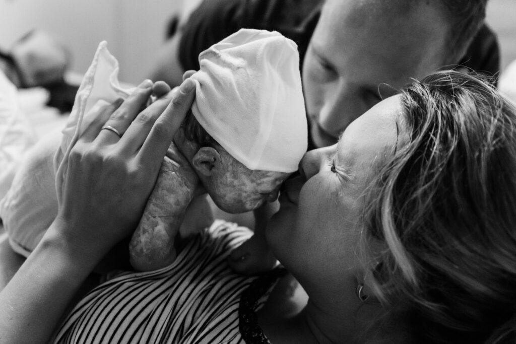 Eerste kus voor pasgeboren baby van moeder emotioneel moment gelukkig mama bevallingsfotografie