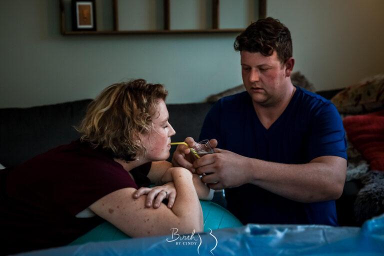 Bevalling papa biedt slokje drinken aan geboortefotografie